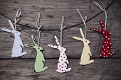 picture of easter bunnies  - Five Colorful Easter Bunnies Hanging On A Line Which Are Dotted And Striped On Brown Wooden Vintage Or Rustic Background For Easter Greetings And Happy Easter - JPG