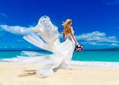 foto of sunbather  - beautiful blond fiancee in white wedding dress with big long white train and with wedding bouquet stand on shore sea - JPG