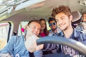 image of sun flare  - Young people having vacation enjoying fun driving car - JPG