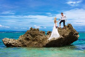 foto of under sea  - Happy bride and groom having fun on a tropical beach under the palm trees - JPG