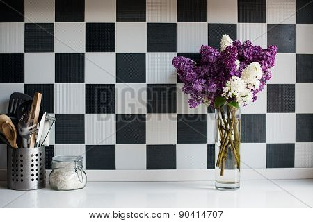 lilacs in a vase and kitchen utensils