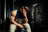 stock photo of dumbbells  - tired bodybuilder athlete with protein shaker and towel with dumbbells - JPG