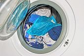 foto of tilt  - front view of a washing machine with open door and dirty linen - JPG