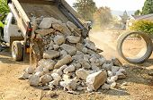 image of dump_truck  - A small dump truck dumps concrete pieces during repair work following a broken water main leak from a fire hydrant base - JPG