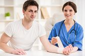 foto of bandage  - Young attractive female doctor with stethoscope bandaging hand of male patient.