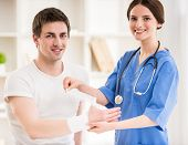 picture of bandage  - Young attractive female doctor with stethoscope bandaging hand of male patient - JPG