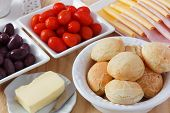 foto of brazilian food  - Brazilian snack pao de queijo (cheese bread) on white plate with cheese ham butter cherry tomato and olives on wooden table. Selective focus ** Note: Shallow depth of field - JPG