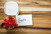 image of milk glass  - view form a above at a stack of cookies and a glass with milk with a white note for santa - JPG