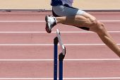foto of leaping  - A male athlete leaping the hurdles on a track - JPG