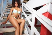 picture of beach hut  - Attractive woman posing by a lifeguard hut in Miami Beach - JPG