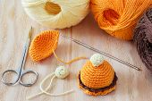 image of thread-making  - Making of handmade colorful crochet toys sweets with skein on wooden table - JPG