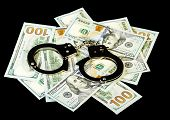 picture of handcuffs  - Handcuffs on dollar money bills isolated on black - JPG