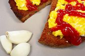 picture of scrambled eggs  - two pieces of fried bread with scrambled egg and garlic on plate - JPG