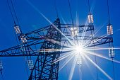 image of voltage  - a high voltage towers for power against blue sky and sun rays - JPG