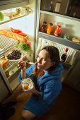 image of refrigerator  - fun woman eating sweet dessert near refrigerator - JPG