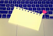 stock photo of pegging  - Laptop keyboard with small red hearts clothes pegs and sticky note - JPG