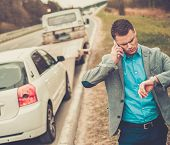 stock photo of tow-truck  - Man calling while tow truck picking up his broken car  - JPG