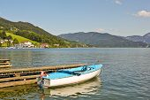 picture of pier a lake  - Boat near pier on Mondsee lake in Austria - JPG