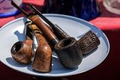 stock photo of tobacco smoke  - Models of pipes for tobacco smoking on white plate - JPG