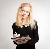 image of hair bow  - Beautiful young blond smiling teenage girl writing down notes on a notepad wearing a black top and a bow in her hair isolated against a white background - JPG