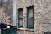 picture of dumpster  - A broken window next to a dumpster in an urban alley - JPG