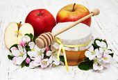 pic of apple tree  - Apples with honey and apple tree flowers on a wooden background - JPG