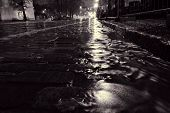 stock photo of rain  - Rain water flowing down a street in down town Helsinki during a nightly autumn storm and creating miniature surge on a cobble street at Unioninkatu in Kaisaniemi district - JPG