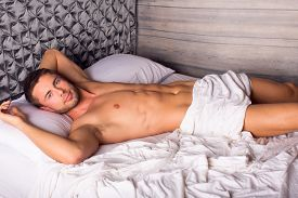 foto of laying-in-bed  - Attractive young man laying in bed - JPG