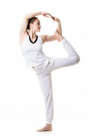 stock photo of sportswear  - Full length portrait of young fitness model in white sportswear doing yoga or pilates training nataradjasana (Dancing Shiva Pose)