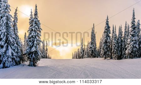 Sun breaking through the clouds on a ski hill