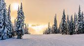 Постер, плакат: Sun breaking through the clouds on a ski hill