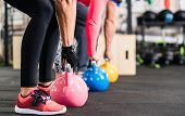 Group having functional fitness training with kettlebell in sport gym poster