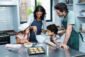 Happy family cooking biscuits together in kitchen at home poster