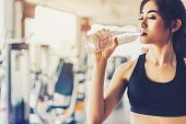 Asian Woman Drinking Pure Drinking Water For Freshness After Workout Or Exercise Training In Fitness poster