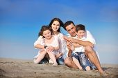 stock photo of family fun  - happy young family have fun and live healthy lifestyle on beach - JPG