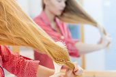 Woman Brushing Her Long Hair In Bathroom poster