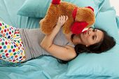 pic of goodnight  - a woman giving her favorite bear a kiss on the nose before they go to bed - JPG