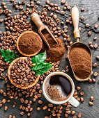 Roasted coffee beans, ground coffee and cup of coffee on wooden table. Top view. poster