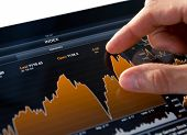 foto of stock market data  - Analyzing stock market graph on a touch screen device - JPG