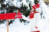 Child With Letter To Santa At Christmas Mail Box In Snow poster