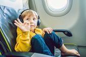 Boy With Headphones Watching And Listening To In Flight Entertainment On Board Airplane poster