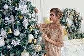 Merry Christmas and Happy New Year. Pretty young woman in evening dress decorates the Christmas tree poster