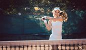 Woman forcefully playing tennis on court poster