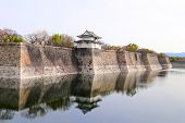 Watch tower and wall of Osaka Castle, Japan. UNESCO world heritage site. Wall and tower are reflecte poster