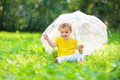 Baby Under Umbrella Playing In Summer Rain. Little Toddler Girl In Garden By Rainy Weather. Outdoor  poster