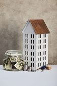House Model, Moneybox With Dollar Banknotes, Keys And Silver Coins On White Table, Real Estate Conce poster