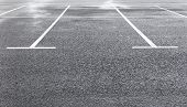 White Marking Lines Of Parking Spots On Wet Asphalt Surface Of Empty Car Park. Copy Space poster