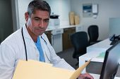 Front view of handsome Caucasian male doctor looking at medical report while working on computer at  poster