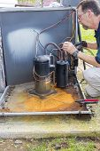 stock photo of hvac  - HVAC tech is removing ac compressor  - JPG