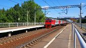 Red Suburban Train Arrives At Station In Summer On Sunny Day. Railway Platform With Train En Route. poster